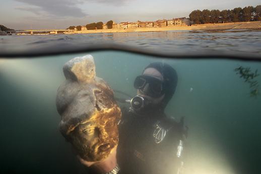 """Photographie """"mi air-mi eau"""" realisee à l'aide d'un caisson sous-marin. Un plongeur de l'equipe de Luc Long presente la tete en marbre du Dieu Mars tout juste ramenee du lit du fleuve, à quelques dizaines de metres des Quais de Trinquetaille à Arles."""